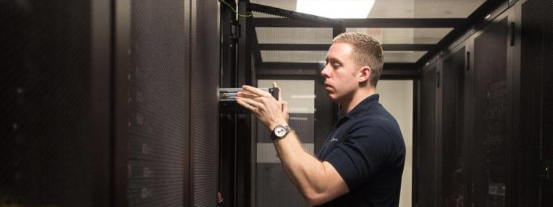 An engineer racking up a server