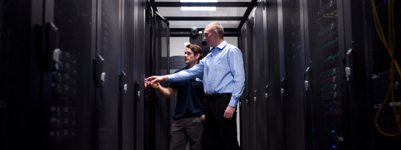 2 engineers looking into a server rack in a data centre